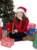 Considerado joven sentada cerca de árbol de Navidad — Foto de Stock