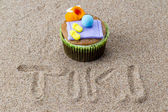 View of cupcake with decorative miniatures toppings on sand with — Stock Photo