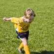 Boy in yellow kicking football — Stock Photo