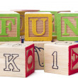 Close up image of playing cubes arranged to form a word fun — Stock Photo