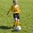 Elementary child playing football — Stock Photo