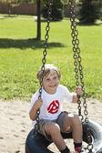 Milý chlapeček, houpající se na pneumatiku swingタイヤのブランコに乗って揺れてかわいい男の子 — Stock fotografie