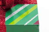 Cropped image of red shiny ribbon on green christmas gift box — Foto de Stock