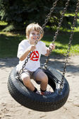 Bonito rapaz loiro balançando no baloiço — Foto Stock
