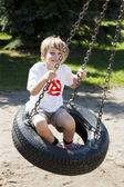 轮胎秋千上摇摆的可爱金发男孩 — 图库照片