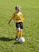 Elementary child playing football — Stock Photo