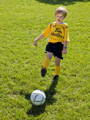 Elementary boy playing soccer — Stock Photo