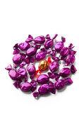 Gouden hard candy geregeld tussen paarse snoepjes — Stockfoto