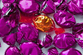 Shiny golden candy with shiny purple hard candies — Stock Photo