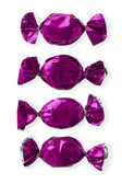 Shiny purple hard candies arranged side by side over white backg — Stock Photo