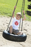Smiling elementary boy sitting on tire swing — Stock Photo