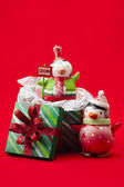 View of christmas gifts box and penguin toys over red background — Stock Photo