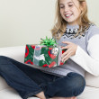 Smiling girl holding her christmas gift — Stock Photo