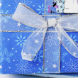 Knot of shiny ribbon on blue christmas gift box — Stock Photo #19866101