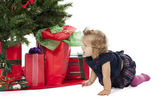 A baby girl crawling by the christmas tree — Foto Stock