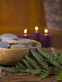 A bowl with spa stones and lighted candle — Stock Photo