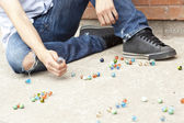 A boy playing marbles on the street — Stock Photo