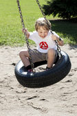 Felice ragazzo elementare dondolando sull'altalena pneumatico — Foto Stock