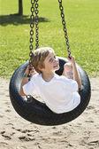 Bakifrån av en pojke som svängande på däck swing — Stockfoto