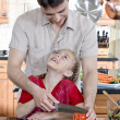 Father and daughter slicing tomato — Stock Photo