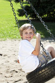 Side view of a boy swinging on tire swing — Stock Photo