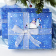 Snowman sticker on blue christmas gift box - Stock Photo