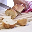 A baker slicing a baguette roll — Stock Photo