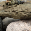 A sniper miniature lying on the rocks - Stock Photo