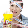 A woman holding popcorn and wrapped by movie tickets — Stock Photo