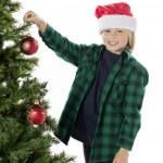 Adorable boy decorating tree — Stock Photo #20247599