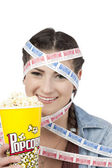 A smiling woman with movie tickets and holding popcorn — Stock Photo