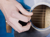 Acoustic guitar and hand — Stock Photo