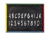 Alphabet letters and numbers written on slate board — Stock Photo