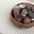 Assorted chocolate in wooden bowl - Stock Photo