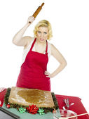 Angry young woman holding rolling pin — Stock Photo