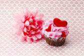 A pink flower beside a pink cupcake with hearts in it — Stock Photo