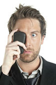 A shocked man with cellphone covering her eye — Stock Photo