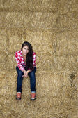 Attractive girl sitting on bales of hay — Stock Photo