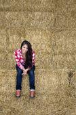 Atrakcyjna dziewczyna siedzi na bele siana — Zdjęcie stockowe