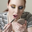 Woman applying lipstick - Stockfoto