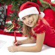 A girl writing her christmas list to santa - Stock Photo