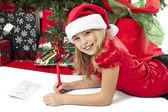Dívka psaní seznam její vánoční santa — Stock fotografie