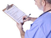 A male doctor with a medical clipboard writing — Stock Photo