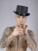 Un hombre con tatuaje fumando un cigarrillo — Foto de Stock