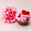 Stock Photo: A pink flower beside a pink cupcake with hearts in it