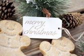 A merry christmas tag among gingerbread men and pine cones — Stock Photo