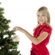 A young girl putting ornaments on a christmas tree — Stock Photo