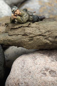 A sniper miniature lying on the rocks — Stock Photo