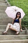 Ein junges mädchen mit regenschirm auf der treppe — Stockfoto