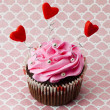 A strawberry cupcake with heart shapes and beads — Stock Photo